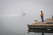 Sherrills Ford, NC - Charlie Glassey of Terrell and his dog Hotrod watch from the Lake Norman Marina dock as the towboat makes a test run in the morning fog prior to the 33rd Annual Lake Norman New Years Day Barefoot Challenge. <br />