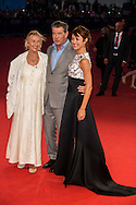 (L to R) Producer Beau St Clair, US-Irish actor Pierce Brosnan and French actress and model Olga Kurylenko pose on the red carpet as they arrive for the screening of 'The November Man' during the 40th Deauville American Film Festival on September 5, 2014 in Deauville,