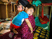 """25 JANUARY 2014 - BANG LUANG, NAKHON PATHOM, THAILAND: A member of the Sing Tong Teochew opera troupe comforts her baby before a show. The Sing Tong Teochew opera troupe has been together for 60 years and travels through central Thailand and Bangkok performing for mostly ethnic Chinese audiences.  Chinese opera was once very popular in Thailand, where it is called """"Ngiew."""" It is usually performed in the Teochew language. Millions of Chinese emigrated to Thailand (then Siam) in the 18th and 19th centuries and brought their cultural practices with them. Recently the popularity of ngiew has faded as people turn to performances of opera on DVD or movies. There are still as many 30 Chinese opera troupes left in Bangkok and its environs. They are especially busy during Chinese New Year when travel from Chinese temple to Chinese temple performing on stages they put up in streets near the temple, sometimes sleeping on hammocks they sling under their stage.     PHOTO BY JACK KURTZ"""