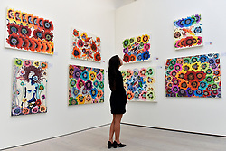 © Licensed to London News Pictures. 12/09/2018. LONDON, UK. A staff member views works by Yang Okkyung (South Korea) at the preview of START, a contemporary art fair comprising eclectic works from a variety of international emerging artists.  The fair takes place at the Saatchi Gallery in Chelsea 13 to 16 September 2018.  Photo credit: Stephen Chung/LNP