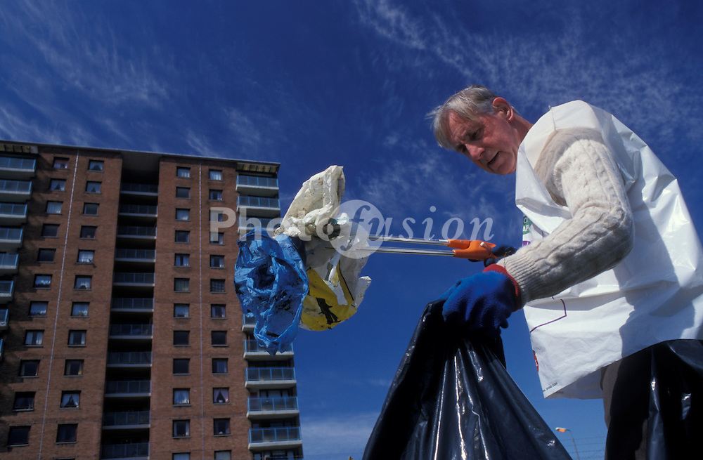 Man picking up litter on housing estate; community clean up; Paisley; Scotland