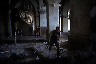 SYRIA, ALEPPO. Syrian rebel fighters run in a damaged section of the Umayyad Mosque complex in the old part of Syria's northern city of Aleppo.  ALESSIO ROMENZI
