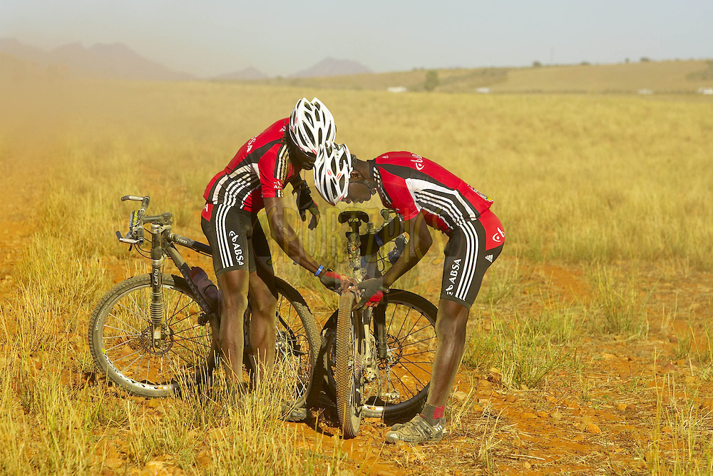 WESTERN CAPE, SOUTH AFRICA -  30 March 2008, David Kinjah Njau and Davidson Kamau Kihagi of Absa Safari Simbaz fix a puncture during stage two of the 2008 Absa Cape Epic Mountain Bike stage race from Saasveld Campus Nelson Mandela Metropolitan University in George to Calitzdorp Spa, Calitzdorp in the Western Cape, South Africa..Photo by Gary Perkin/SPORTZPICS