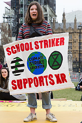 London, UK. 23rd April 2019. A school striker addresses climate change activists from Extinction Rebellion at an assembly in Parliament Square to discuss the preparation and delivery of activists' letters requesting meetings to discuss climate change with Members of Parliament.