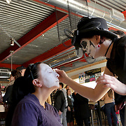 Anna Gamel paints Caroline Park's face at Flytrap Brewing during the Day of the Dead Art Crawl in the Brooklyn Arts District. (Jason A. Frizzelle)