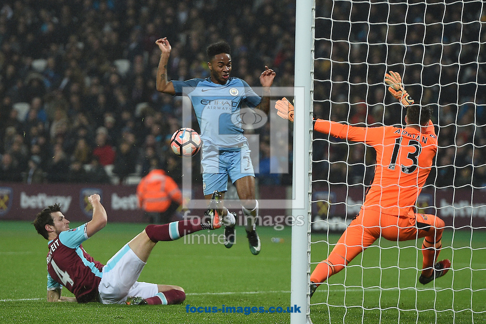 Manchester City's Raheem Sterling scores their second goal despite the attention of West Ham United's Havard Nordtveit (left) and goalkeeper Adrian during the third round of the FA Cup at the London Stadium, Stratford<br /> Picture by Daniel Hambury/Focus Images Ltd 07813022858<br /> 06/01/2017
