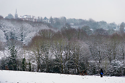 A lone walker crosses the snowy landscape as people and their pets enjoy the three inches of snow on Hampstead Heath in North London. Hampstead, London, February 01 2019.