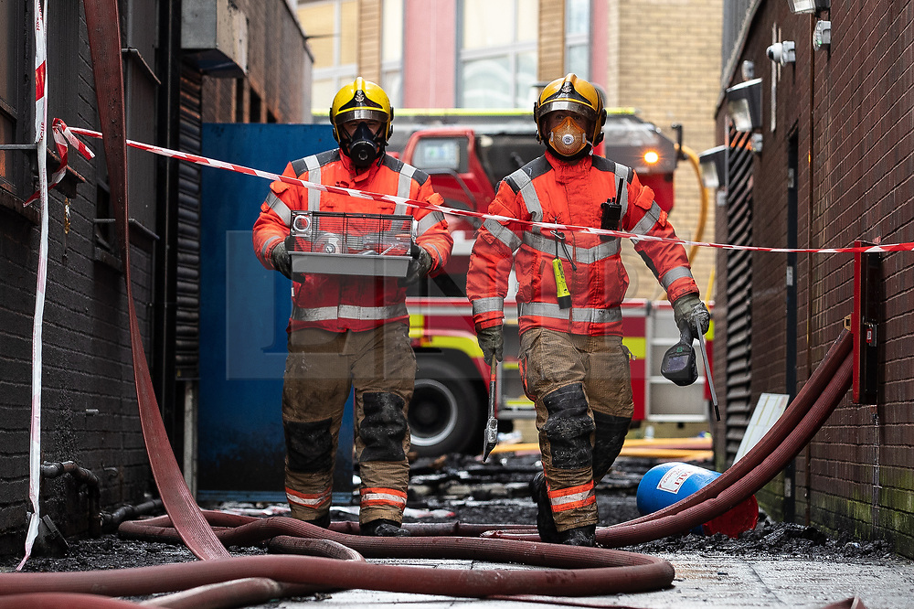 "© Licensed to London News Pictures. 16/11/2019. Bolton, UK. Firefighters rescue a resident's pet hamster as they work at the scene where a fire broke out overnight (15th/16th November 2019) at a block of flats known as "" The Cube "" , in Bolton Town Centre . At least two people are known to have been treated by paramedics at the scene of the six-story , block which is occupied by students of the University of Bolton . Photo credit: Joel Goodman/LNP"