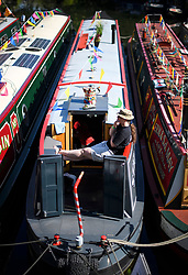 © Licensed to London News Pictures. 06/05/2018. London, UK. A boat owner enjoys the sunshine at day two of the Canalway Cavalcade festival takes place in Little Venice, West London on Sunday,  May 6th 2018. Inland Waterways Association's annual gathering of canal boats brings around 130 decorated boats together in Little Venice's canals on May bank holiday weekend. Photo credit: Ben Cawthra/LNP