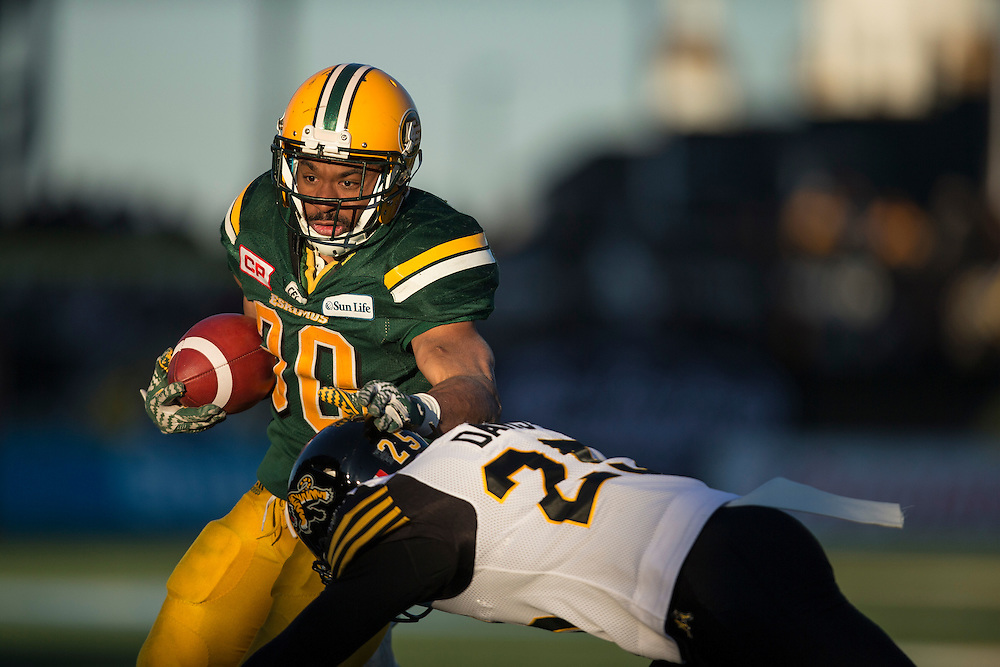 Edmonton's John White tries to avoid a hit by Hamilton's Chris Davis during the 4th quarter of the CFL's Eastern semi-final between the Ticats and the Eskimos in Hamilton on Sunday November 13, 2016.  (CFL PHOTO - Geoff Robins )