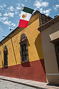 Mexican flag flutter against a blue sky and classic colonial building along Calle Quebrada in the historic district of San Miguel de Allende, Mexico.