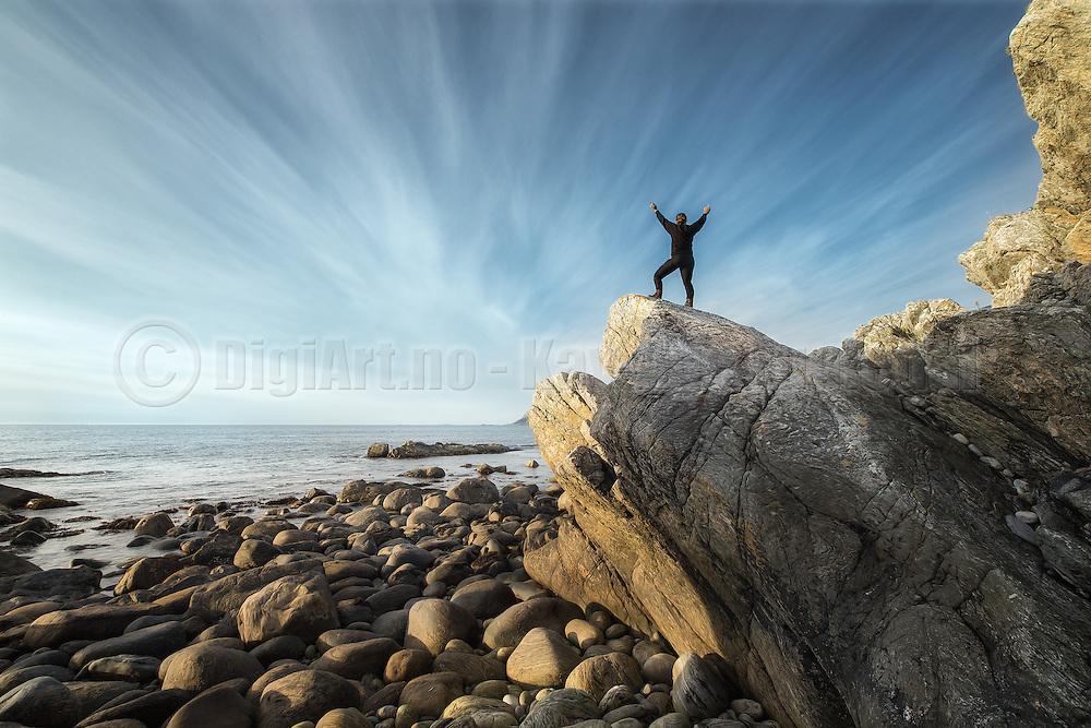 Women on top of a clip salutes the ocean, with a dramatic sky in the background| Dame på toppen av en klippe hilser til havet, med en dramatisk himmel i bakgrunnen.