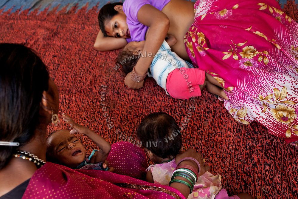 A mother is feeding breast milk to her malnourished child (right) while lying on the floor of a feeding centre run by UNICEF in the town Shivpuri, Madhya Pradesh, India.