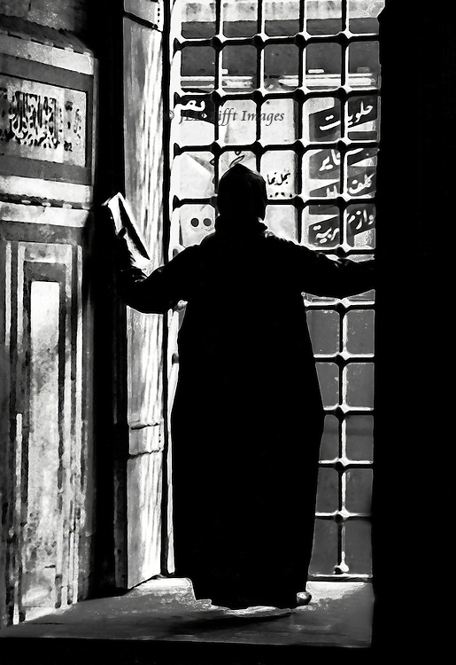 The mosque caretaker opens the interior shutters to the morning.  His gowned figure is silhouetted against the iron grillwork of the window.  A folded newspaper is in his left hand.