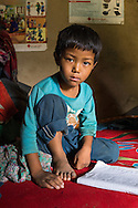 Sonam Tamang (7) poses for a portrait in his temporary shelter in Kavre, Bagmati, Nepal on 30 June 2015.  His mother, Kalpana, a widow with 3 children, has been supported by SOS Children's Villages for many years now and had receive the Home-in-a-Box after the earthquake destroyed her house, almost killing her two daughters. She now lives in a temporary shelter, sharing her dwelling with farm animals, and is trying to make ends meet by weaving bamboo baskets to supplement the financial assistance provided by SOS Childrens Villages. The NGO mostly supports her children's welfare and schooling as well as provides her with essential household and schooling items like kitchen utensils and school books and uniforms. Photo by Suzanne Lee for SOS Children's Villages