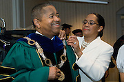 OU President Roderick McDavis receives assistance with his gown from wife Deborah McDavis prior to the June 7 College of Osteopathic Medicine graduation.