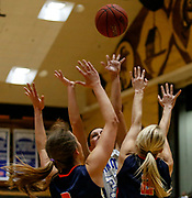 Dakota Wesleyan's Chesney Nagel (32) shoots over the defense of Midland University's Megan Kucks (3) and Makenna Sullivan (2) during a Great Plains Athletic Conference game on Sunday at the Corn Palace. (Matt Gade / Republic)