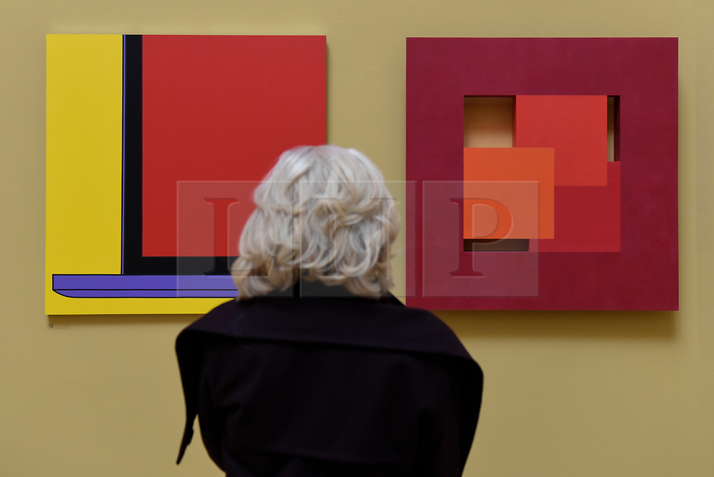 "© Licensed to London News Pictures. 08/06/2017. London, UK. A visitor views (L to R) ""Untitled (Yellow Laptop Fragment)"" by Sir Michael-Craig Martin RA (GBP40,000) and ""Thirds"" by John Carter RA (GBP10,000). Preview of the Summer Exhibition 2017 at the Royal Academy of Arts in Piccadilly.  Co-ordinated by Royal Academician Eileen Cooper, the 249th Summer Exhibition is the world's largest open submission exhibition with around 1,100 works on display by high profile and up and coming artists.<br />  Photo credit : Stephen Chung/LNP"