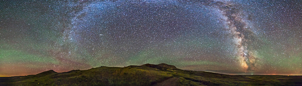A 5-section 180° panorama of the 70 Mile Butte area of Grasslands National Park, Saskatchewan, with the Milky Way at left and right. Some green bands of airglow are also visible. I shot this with the 14mm Rokinon lens in landscape orientation, with the pan segments stitched with PTGui software. Each segment was an 80-second untracked exposure at f/2.8 and ISO 3200 with the Canon 6D.
