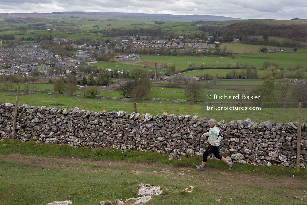 A lady hill runner jogs along a dry stone wall on a footpath above the town of Settle, on 13th April 2017, Yorkshire, England.