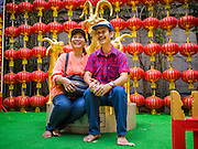 "19 FEBRUARY 2015 - BANGKOK, THAILAND: A couple is photographed next to a statue of a goat on Chinese New Year at Wat Mangkon Kamalawat in Bangkok. 2015 is the Year of Goat in the Chinese zodiac. The Goat is the eighth sign in Chinese astrology and ""8"" is considered to be a lucky number. It symbolizes wisdom, fortune and prosperity. Ethnic Chinese make up nearly 15% of the Thai population. Chinese New Year (also called Tet or Lunar New Year) is widely celebrated in Thailand, especially in urban areas that have large Chinese populations.    PHOTO BY JACK KURTZ"
