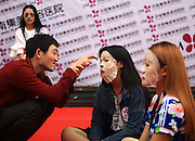 JINAN, CHINA - APRIL 29: (CHINA OUT)<br /> <br /> Staring Contest With Facial Masks <br /> <br /> An organizer tantalizes a participant during Staring Contest at Luoyuan Street on April 29, 2105 in Jinan, Shandong province of China. A Staring Contest held by a plastic surgery hospital attracted nearly 50 boys and girls that participants should wear facial masks and could not move or even other facial expressions. <br /> ©Exclusivepix Media