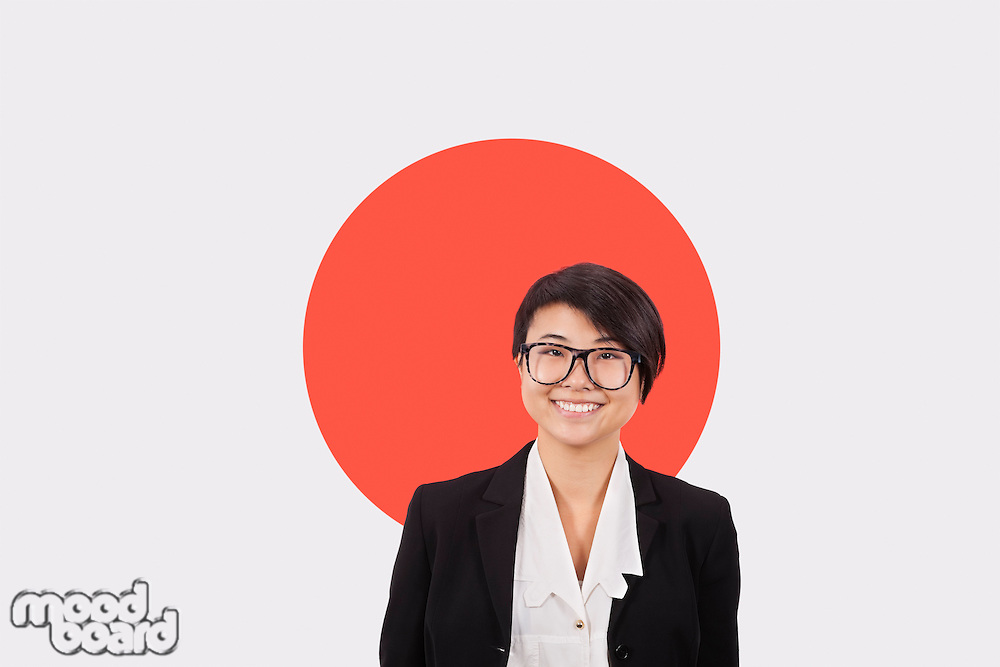 Portrait of young businesswoman smiling over Japanese flag
