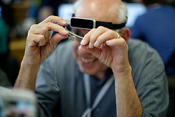With help of Google Glass paired with a 3D motion sensor 'subject matter' Howard Bilofsky, tries to thread a needle.