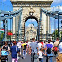 """People Crossing Chain Bridge in Budapest, Hungary <br /> Prior to the mid-19th century, the only way to cross the Danube between Buda and Pest was by boat. Count István Széchenyi fixed the problem. He was an influential politician who was called the Greatest Hungarian. Széchenyi spearheaded several projects to tame the Danube for navigation and transportation. He hired William Tierney Clark to design a permanent bridge. The 1,230 foot span was Europe's largest when it opened in 1849. The Hungarian name is Széchenyi Iánchid. The latter word means """"chain"""" in recognition of the iron cables."""