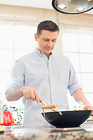 Middle-aged man cooking in kitchen