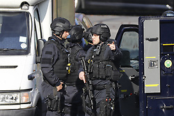 © Licensed to London News Pictures. 23/10/2016. London, UK. Armed police are seen in front of a house in Lancaster Road in Northolt on Sunday, 23 October 2016. Police surround the address after a report of concerns for the occupant and hazardous items inside the property. Police believe a man is still inside the house. Photo credit: Tolga Akmen/LNP