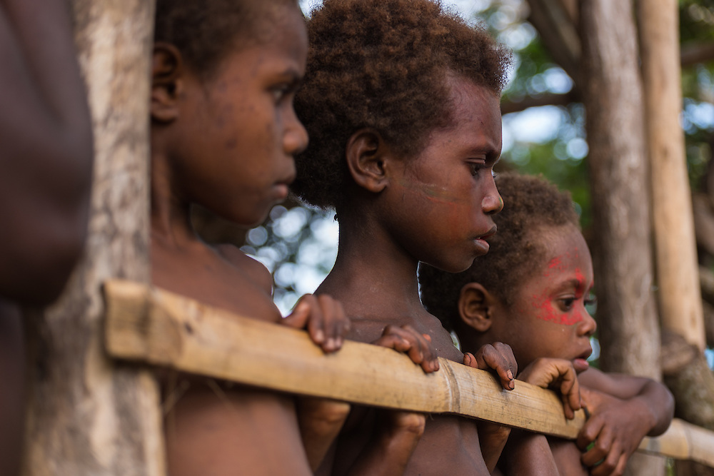 Three children looking over a pence, Tannah, Vanuatu.