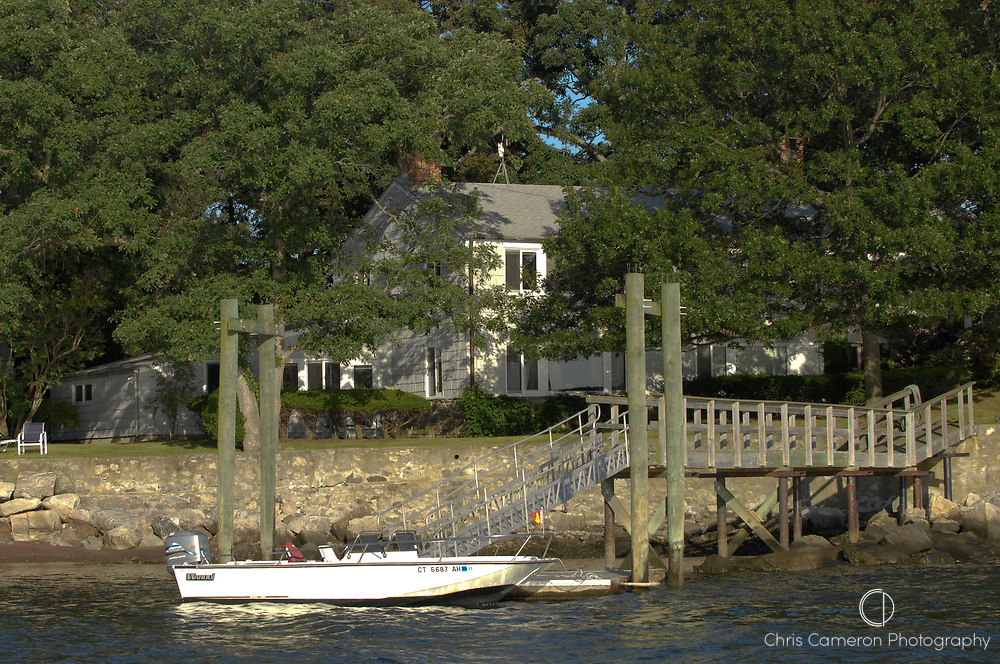 House with jetty and Boston Whaler fishing boat on the banks of Five mile River. Long Island Sound, Connecticut. USA