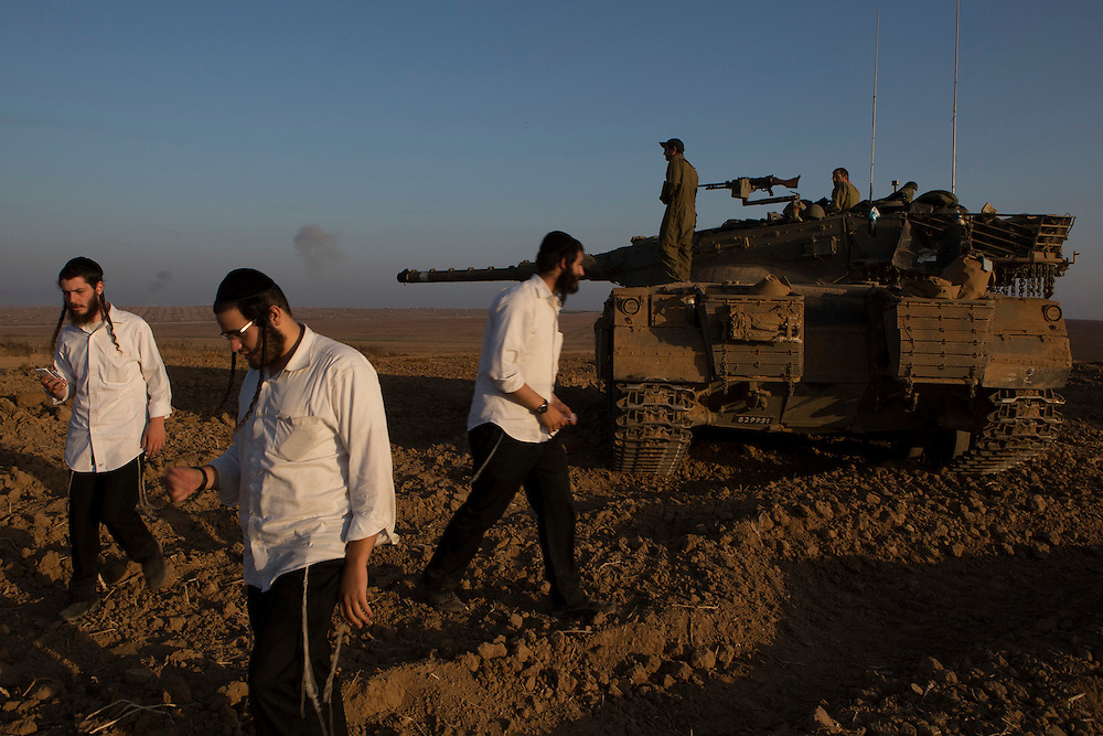 Israeli men walk close to a tank as billows of smoke rise from Gaza, near the border with the Gaza Strip.