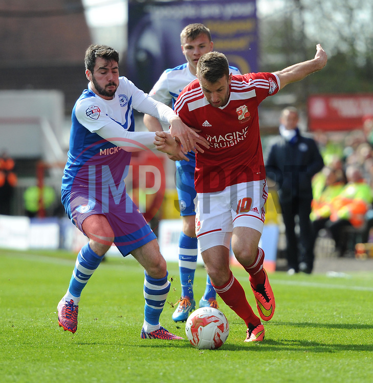 Peterborough United's Michael Smith battles with Swindon Town's Andy Williams - Photo mandatory by-line: Paul Knight/JMP - Mobile: 07966 386802 - 11/04/2015 - SPORT - Football - Swindon - The County Ground - Swindon Town v Peterborough United - Sky Bet League One