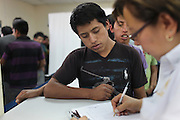 Salomon Actún Ixcoy, 18, from Clementoro Hamlet in Aguacatán, Huehuetenango, signs up for complementary transport up to Huehuetenango City at the Migration Office in Guatemala City's La Aurora Airport after having been deported from the United States. Salomon, whose main language is Quiché, claims he was caught by the border patrol while crossing the Rio Grande near Reynosa, Mexico, and will try again once he gets the chance as there are no economic opportunities in his hometown. Guatemala City, Guatemala. May 17, 2013.
