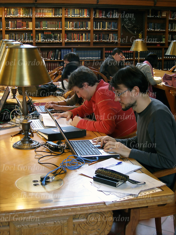 Reference Room in the Fifth Avenue branch of the New York Public Library. College students researching in library,using personal computers and library computer to researching on the internet.