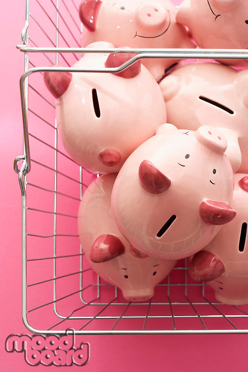 Shopping cart with piggy banks on pink background view from above