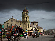 24 JANUARY 2018 - GUINOBATAN, ALBAY, PHILIPPINES: People wear breathing filters as they pass the church during a volcanic ash fall in Guinobatan. An ash cloud from the volcano was over the town most of the afternoon. The Mayon volcano continued to erupt Tuesday night and Wednesday forcing the Albay provincial government to order more evacuations. By Wednesday evening (Philippine time) more than 60,000 people had been evacuated from communities around the volcano to shelters outside of the 8 kilometer danger zone. Additionally, ash falls continued to disrupt life beyond the danger zones. Several airports in the region, including the airport in Legazpi, the busiest airport in the region, are closed indefinitely because of the amount of ash the volcano has thrown into the air.    PHOTO BY JACK KURTZ