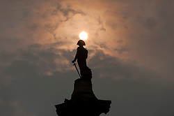 © Licensed to London News Pictures. 17/10/2017. London, UK. The sun makes an appearance through low clouds over Nelson's Column as dust, brought by the winds of Storm Ophelia, continue to give the sky an colour. Photo credit : Stephen Chung/LNP