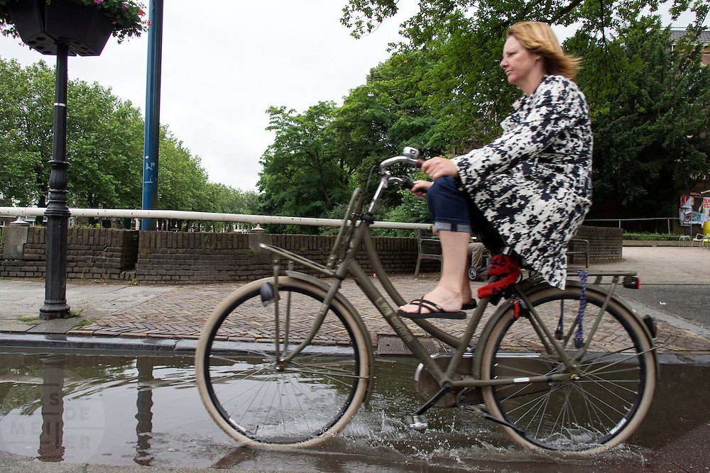 Fietsers trekken hun benen op om hun voeten droog te houden als ze door een plas moeten rijden.<br />