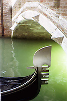 Artistic photo of a gondola passing under a bridge on a canal in Venice, Italy.