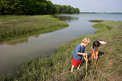Young children (age 5) explore a tidal creek and marsh in Marquoit Bay in Brunswick, Maine.