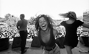 Two women dancing on stage while a security man sprays the crowd with water at Bindoon Festival W.Australia 1990's