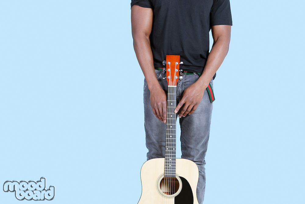 Mid section of an African American man with guitar over light blue background