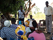 Helen Kongai and Stanslaus Omoding leading a group session with Send a Cow's Aliasit Zion Group. They are meetng in the shade of a mango tree.