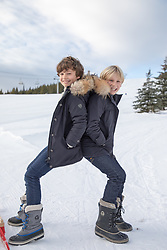 twin boys on a ski slope enjoying time together