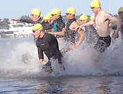 The men's group of competitors charges into the waters of Lake Michigan's Little Traverse Bay at the start of the inaugural Little Traverse Triathlon in Harbor Springs, Michigan.