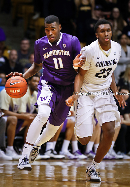 SHOT 1/22/15 9:10:19 PM - Washington's Mike Anderson #11 drives around Colorado's Jaron Hopkins #23 during their regular season Pac-12 basketball game at the Coors Events Center in Boulder, Co. Washington won the game 52-50 on a shot with less than a second to play in the game. (Photo by Marc Piscotty / © 2015)