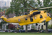 A Royal Air Force Sea King Westland helicopter takes-off after a medical mission to deliver a patient to Kings College Hospital in Camberwell. As locals look on at the aircraft as it lifts off from Ruskin Park, Lambeth in south London, the yellow RAF search and rescue aircraft (SAR) leaves to return to base. Both RAF, Royal Navy and London air ambulances regularly use this public space for emergency transporting of casualties to the NHS Trust A&E department.